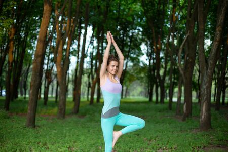 Young smiling attractive yogi woman practicing yoga, standing in Vrksasana exercise, Tree pose. Thin brunette girl plays sports and performs beautiful and sophisticated yoga poses in a summer park. 写真素材