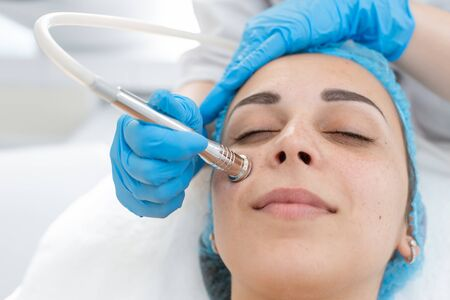 Beautician procedure diamond microdermabrasion patient face. A young girl is undergoing a course of spa treatments in the office of a beautician. Moisturizing, cleaning and facial skin care. Cosmetic procedures.