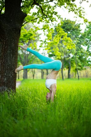 Thin brunette girl plays sports and performs beautiful and sophisticated yoga poses in a summer park. Green lush forest on the background. A woman stands on the hands of a tree.