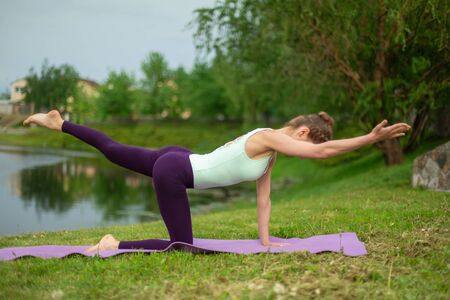 Slim young brunette yogi performs no complicated yoga exercises on the green grass in summer against the background of nature.