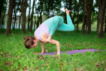 Thin brunette girl plays sports and performs beautiful and sophisticated yoga poses in a summer park. Green lush forest on the background. Woman doing exercises on a yoga mat.