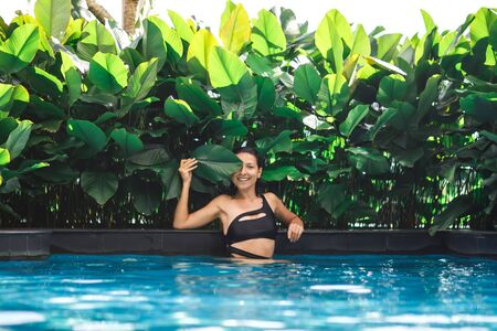 Portrait of young sexy caucasian woman in swimming pool with green plants. Imagens