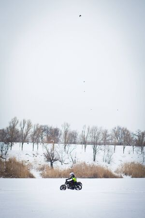 A guy rides a motorcycle on a frozen lake. Stockfoto