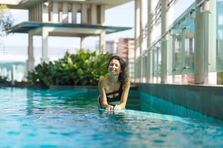 Portrait of a sexy smiling caucasian woman in a swimsuit lay on the edge of a rooftop pool with green bushes and city views. Asia weekend. Imagens