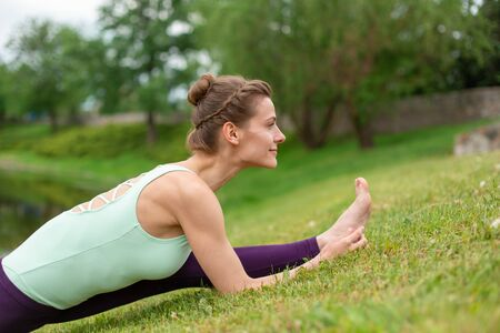 Slender young brunette yogi performs challenging yoga exercises on the green grass in the summer against the backdrop of nature.