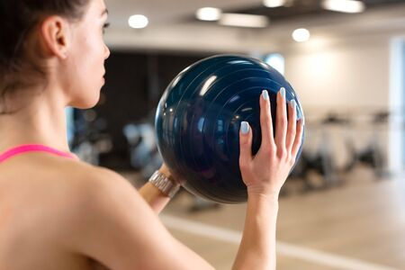 Beautiful young slim woman in sportwear doing some gymnastics at the gym with medball.
