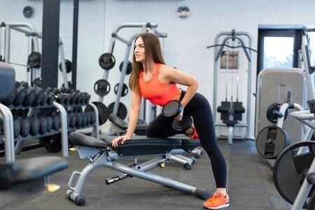 szczupła kobieta ćwiczenia z hantlami na ławce w siłowni. Zdjęcie Seryjne