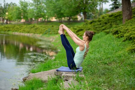 Thin brunette girl sitting in Both big toe exercise, Paripurna Navasana pose  in a summer park. Green forest on the background. Woman doing exercises on the yoga mat. 写真素材