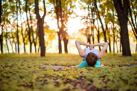 Thin brunette girl plays sports and performs yoga poses in autumn park on a sunset background. Woman doing exercises on the yoga mat. Autumn forest. Soft focus.