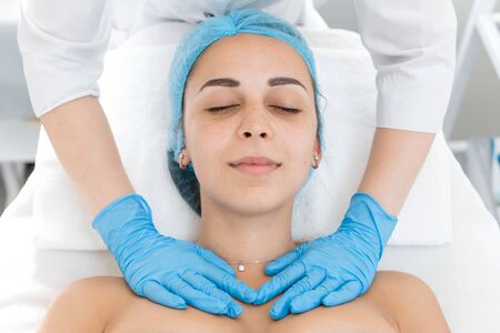 Beautician makes professional massage of the patient's neck. A young girl is undergoing a course of spa treatments in the office of a beautician. Moisturizing, cleaning and facial skin care. Cosmetic procedures.