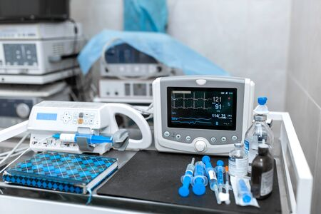 Cardiac monitor and syringe at operating table. Pet surgery. Stock Photo - 128684229