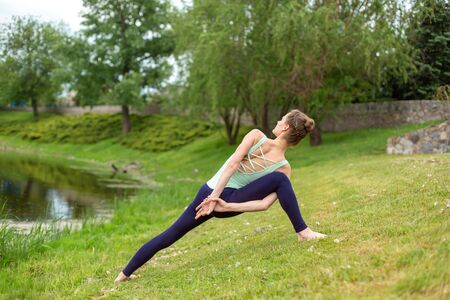 Slender Caucasian brunette girl doing yoga in summer on a green lawn by the river. Banco de Imagens