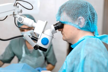 ophthalmologist surgeon looking through surgical microscope doing difficult operation.