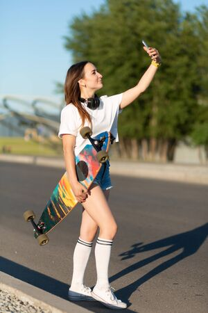 Girl walking with longboard and make selfie on mobile phone.