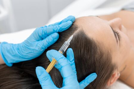 Beautician injections for healthy hair growth. Mesotherapy of the scalp. A young girl is undergoing a course of spa treatments in the office of a beautician. Moisturizing, cleaning and facial skin care. Cosmetic procedures.