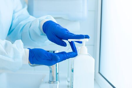 the surgeon sterilizes blue gloves before surgery. Stock Photo
