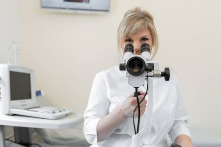 Young female professional gynecologist in the working process, looks into the colposcope.