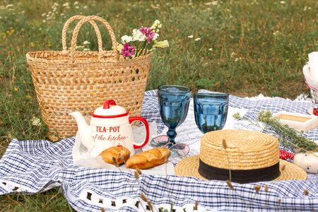 Stylish picnic on the green lawn. Fresh croissants and a teapot with tea on a bedspread near a wicker  hat.  content. 스톡 콘텐츠