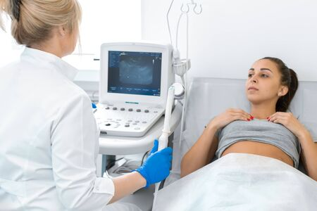 The gynecologist sets up the ultrasound machine and explains to the patient how the study will be performed. Ultrasound of the pelvic organs. Reklamní fotografie