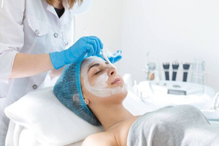 A professional cosmetologist applies a nourishing cream on the patient's face. Moisturizing, cleaning and facial skin care. Cosmetic procedures.