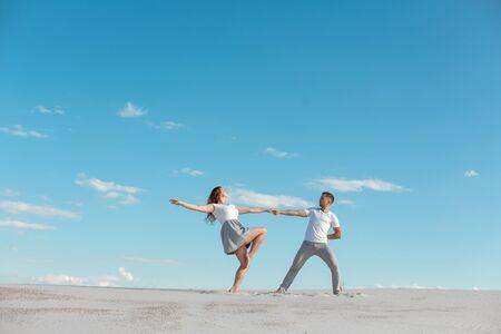 Romantic couple dancing in sand desert at blue sky background. Foto de archivo