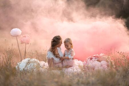 Mom and daughter in pink fairy-tale dresses are sitting in a field surrounded by Big pink decorative flowers. Imagens