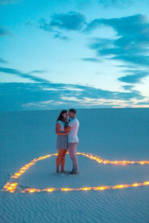 Couple in love romantic hugs in sand desert. Evening, romantic atmosphere, in sand burn candles in form of heart.