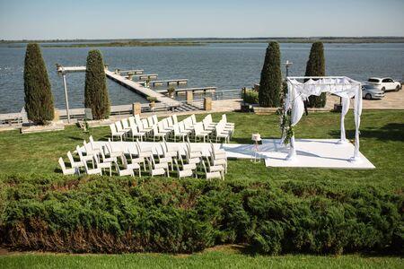 Hermosa boda saliente preparada. Hupa judía en ceremonia de boda romántica, boda al aire libre en la vista del agua del césped. Decoración de boda. Sillas de madera blanca sobre un césped verde. Sillones blancos para invitados.