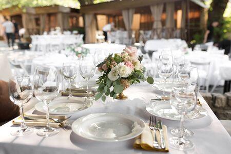 Bruiloft tafel setting versierd met verse bloemen in een koperen vaas. Bruiloft bloemisterij. Bankettafel voor gasten buiten met uitzicht op de groene natuur. Boeket met rozen, eustoma en eucalyptusbladeren. Stockfoto