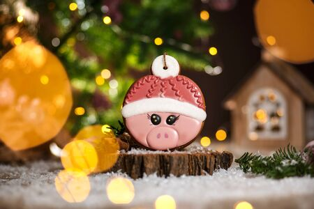 Holiday traditional food bakery. Gingerbread pink pig head in hat in cozy warm decoration with garland lights. Banque d'images - 129565049