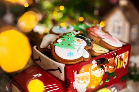 Holiday traditional food bakery. Decorative toy car with christmas Gingerbread cakes in cozy warm decoration with garland lights.