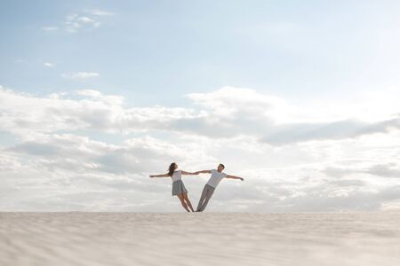 Romantic couple dancing holding each other arms in sand desert. Reklamní fotografie