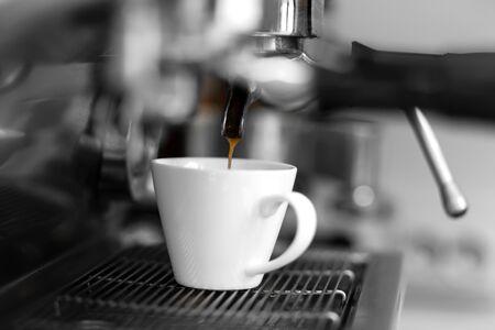 Eine Kaffeemaschine gießt frisch gebrühten heißen Kaffee in eine weiße Tasse.