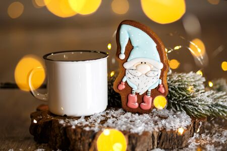 Holiday traditional food bakery. Gingerbread little fairytale gnome in cozy decoration with garland lights and cup of hot coffee.