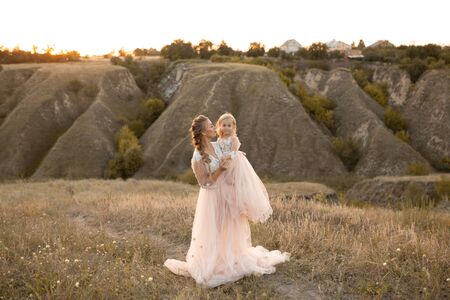 Mom with daughter in pink fairy-tale dresses walk in nature. Little princess childhood.