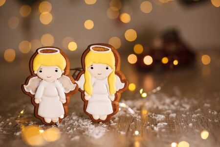 Holiday traditional food bakery. Gingerbread pair of little cute angels boy and girl in cozy warm decoration with garland lights. Фото со стока