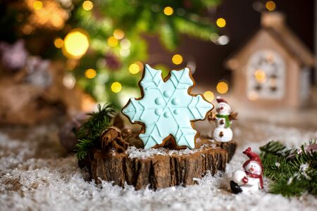 Holiday traditional food bakery. Gingerbread blue snowflake in cozy warm decoration with garland lights. Фото со стока