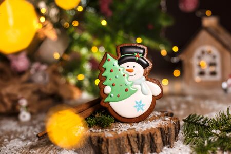 Holiday traditional food bakery. Gingerbread snowman with christmas tree in cozy warm decoration with garland lights.