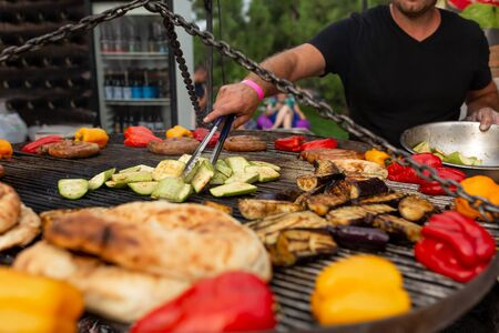 A large round grill on the coals in which grilled color vegetables and fresh meat sausages are cooked. Food and equipment for cooking at a food festival. Фото со стока - 129818245