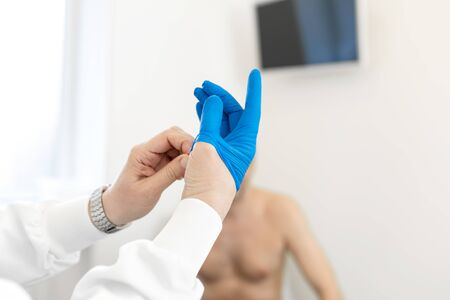 Doctor urologist puts a medical glove on the arm to examine the patients prostate, prostate massage, lymphatic drainage.