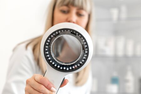 The doctor trichologist dermatologist examines the camera through the dermatoscope. Stock Photo