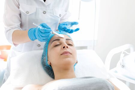 A professional cosmetologist applies a nourishing cream on the patients face. Moisturizing, cleaning and facial skin care. Cosmetic procedures.