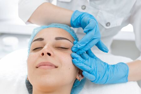 Beautician makes professional massage of the patients face. A young girl is undergoing a course of spa treatments in the office of a beautician. Moisturizing, cleaning and facial skin care. Cosmetic procedures.