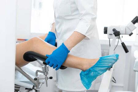 The gynecologist helps the patient to sit in the gynecological chair. Stock Photo