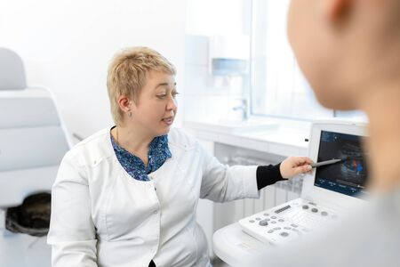 Professional doctor advises the patient young girl after ultrasound.