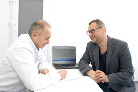doctor urologist advises a male patient in clinic. 写真素材 - 129818063