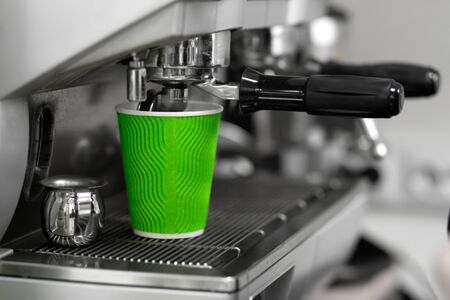 A coffee machine pours a freshly brewed finished drink in a green eco-friendly paper cup to a customer. Barista work in a coffee shop. Stok Fotoğraf