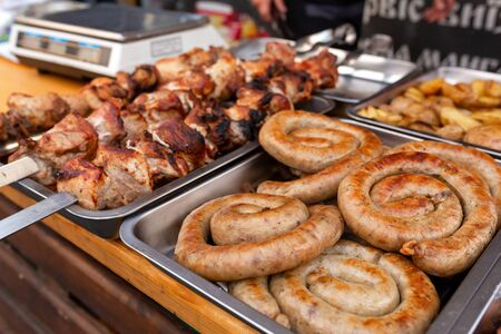 A counter with metal trays containing grilled sausages and meat. Food and cooking equipment at a street food festival. Фото со стока