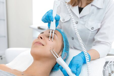 Beautician procedure of microcurrent therapy of the patients face. A young girl is undergoing a course of spa treatments in the office of a beautician. Moisturizing, cleaning and facial skin care. Cosmetic procedures. Banco de Imagens