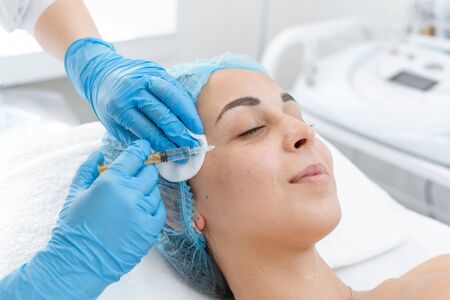 The beautician makes professional rejuvenation vitamin injections for the skin of the patients face. A young girl is undergoing a course of spa treatments in the office of a beautician. Moisturizing, cleaning and facial skin care. Cosmetic procedures.